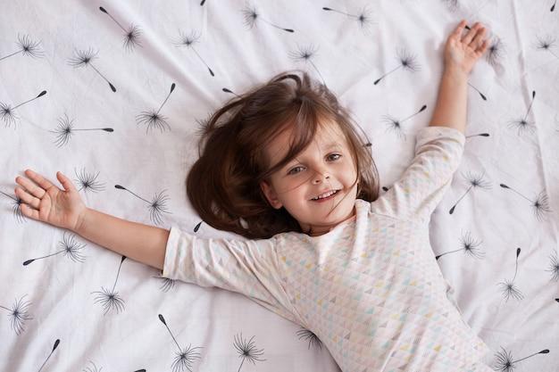 Leuk meisje die thuis spelen terwijl het liggen op deken met paardebloem op bed met slaperige en gelukkige gelaatsuitdrukking, die haar wapens uitspreiden Premium Foto