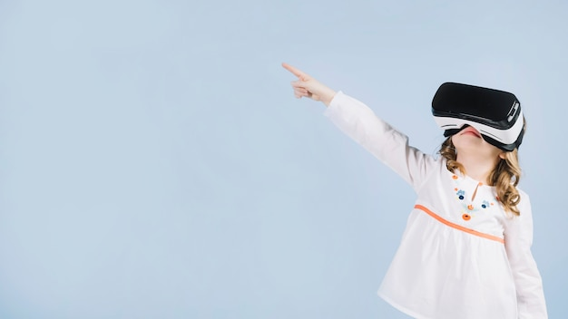 Leuk meisje die virtuele hoofdtelefoon gebruiken die haar vinger richten op iets Gratis Foto