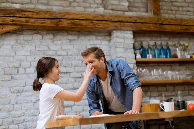 Leuk meisje en haar knappe papa die deegwaren in de keuken voorbereiden Premium Foto