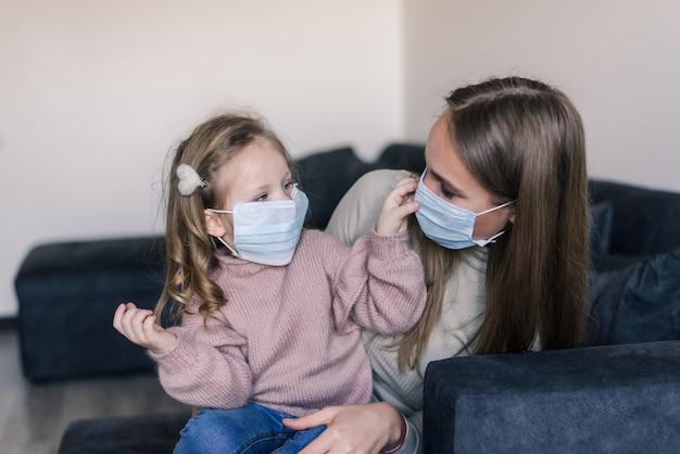 Leuk meisje en moeder die gezichtsmasker dragen, thuis zittend op bed, die droevige peuterdochter troosten Gratis Foto