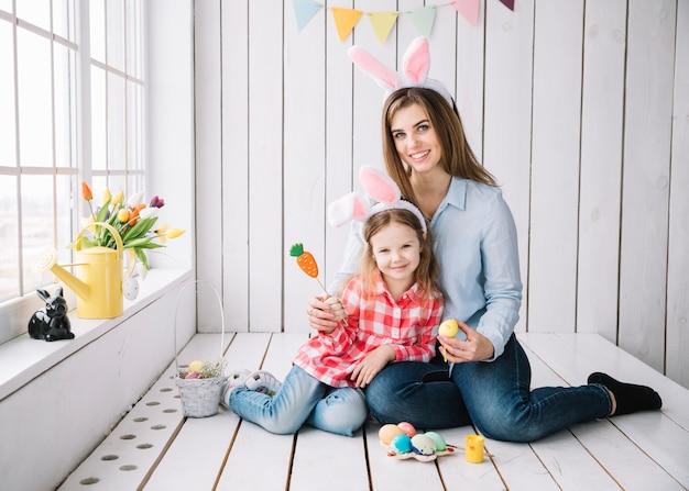 Leuk meisje en moeder in konijntjesoren die met paaseieren zitten Gratis Foto