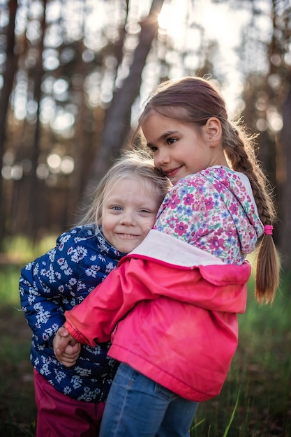 Leuk meisje haar kleine zusje met liefde en tederheid knuffelen tijdens hun wandeling in het bos op herfst, nationale knuffel- en vriendschapsdag, informele levensstijl, buiten Premium Foto