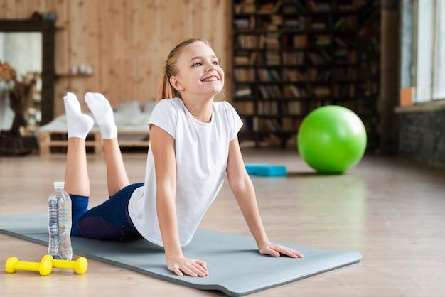 Leuk meisje het beoefenen van yoga op mat Gratis Foto