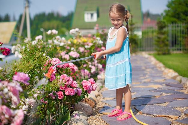 Leuk meisje in blauwe jurk bloemen water geven met een slang in haar tuin Premium Foto