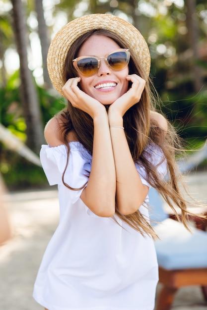 Leuk meisje in bruine zonnebril en strooien hoed glimlacht wijd en houdt haar handen in de buurt van de kin. Gratis Foto
