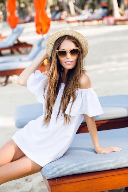 Leuk meisje in bruine zonnebril en strooien hoed glimlacht wijd en houdt haar hoed met een hand vast Gratis Foto