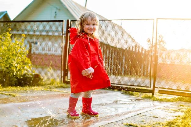Leuk meisje in een rode jas is springen in de plas. de ondergaande warme zomer- of herfstzon. zomer in dorp. Premium Foto