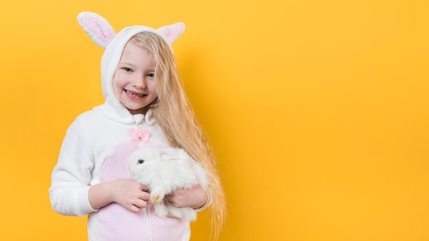 Leuk meisje in konijntjesoren met konijn Gratis Foto