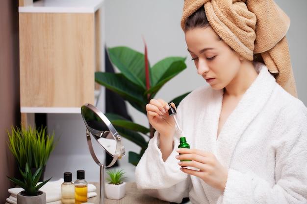 Leuk meisje maakt make-up op het gezicht in de badkamer Premium Foto