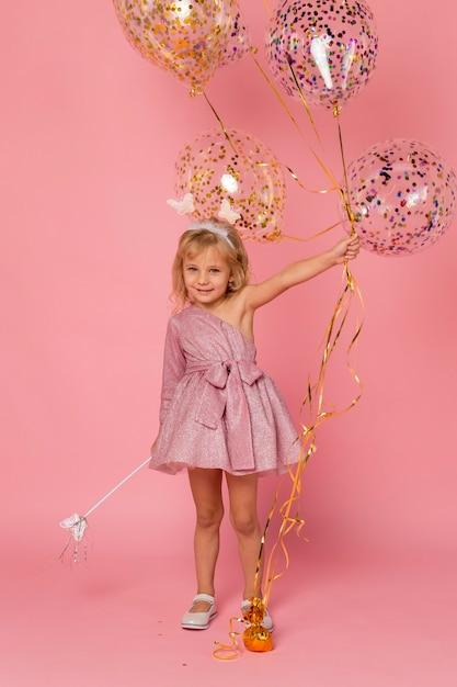 Leuk meisje met ballonnen en toverstaf Gratis Foto