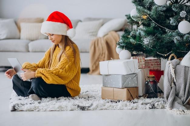 Leuk meisje met behulp van computer door kerstboom Gratis Foto