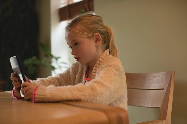 Leuk meisje met behulp van digitale tablet in de woonkamer Gratis Foto