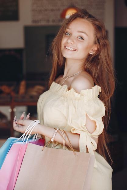 Leuk meisje met boodschappentas in een stad Gratis Foto