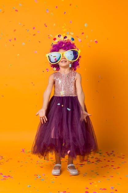 Leuk meisje met clownpruik en confetti Gratis Foto