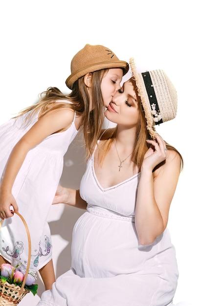 Leuk meisje met een mand met bloemen die naar de moeder leunen en haar wang kust. Gratis Foto