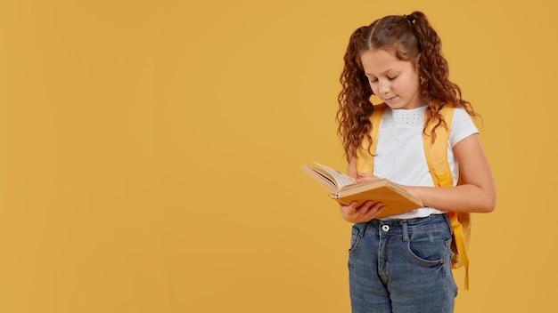 Leuk meisje met gele rugzak en leest Gratis Foto