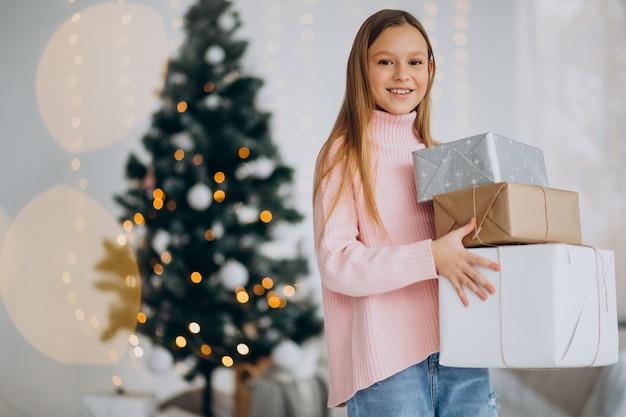 Leuk meisje met kerstcadeautjes door kerstboom Gratis Foto