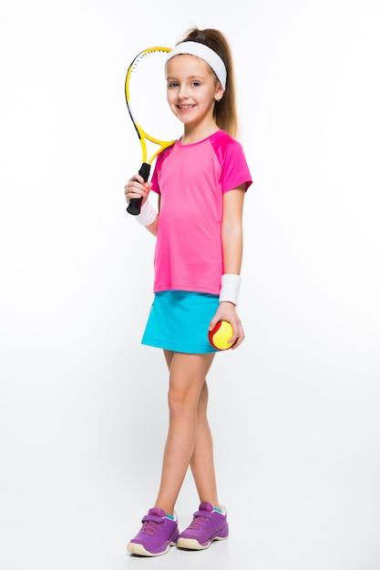 Leuk meisje met tennisracket en bal in haar handen op wit Premium Foto