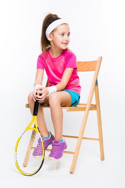 Leuk meisje met tennisracket in haar handen op wit Premium Foto