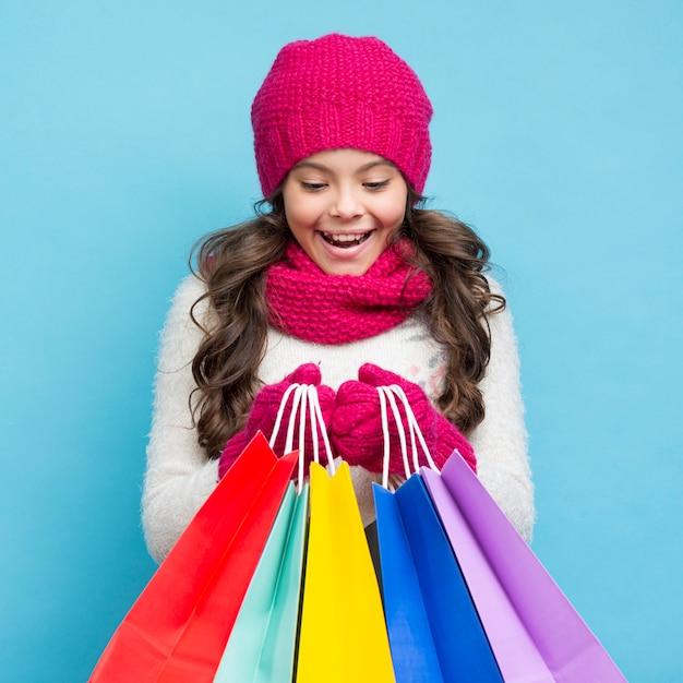 Leuk meisje met winterkleren en boodschappentassen Gratis Foto