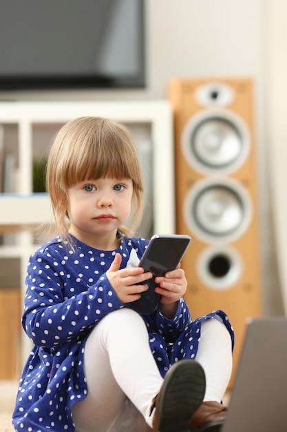 Leuk meisje op het gebruikscellphone van het vloertapijt Premium Foto