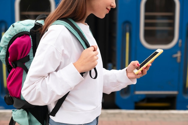 Leuk meisje op het treinstation met haar smartphone Gratis Foto