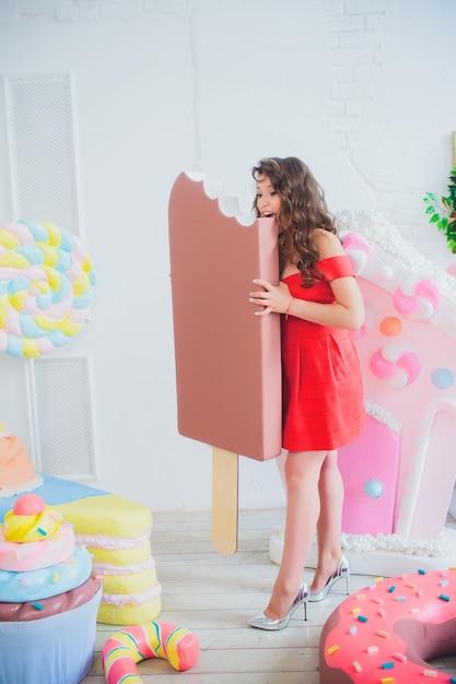 Leuk meisje poseren met roze donuts, gek rond, dessert, slecht eten, kijkt in het gat in de donut, houdt donuts bij de ogen Premium Foto