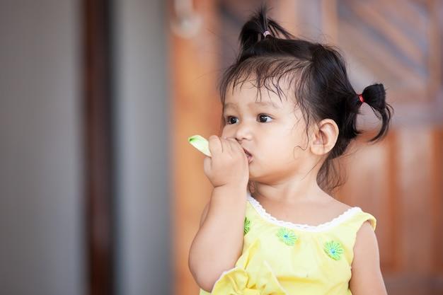 Leuk meisje van het baby aziatisch kind die mango eten Premium Foto