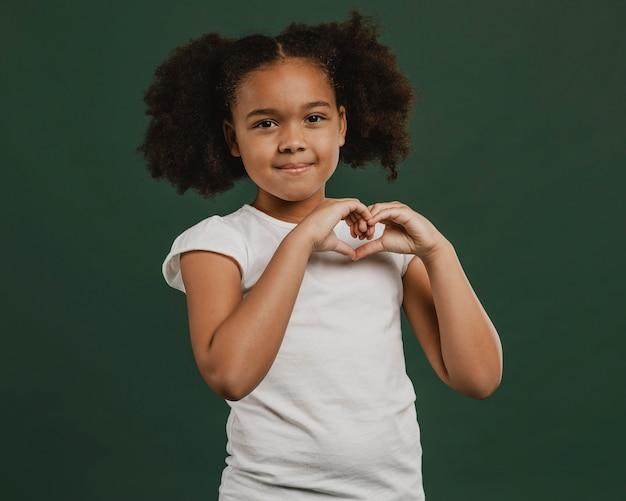 Leuk meisjeskind dat een hartvorm maakt Premium Foto