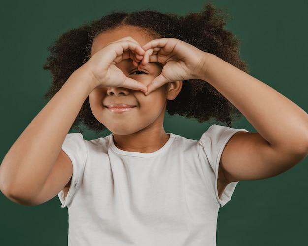 Leuk meisjeskind dat een hartvorm voor haar gezicht maakt Premium Foto
