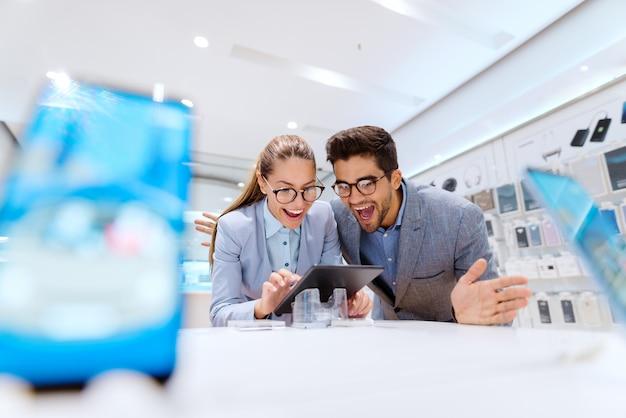 Leuk multicultureel paar in formele slijtage die en nieuwe te kopen tablet glimlachen zoeken. tech store interieur. Premium Foto
