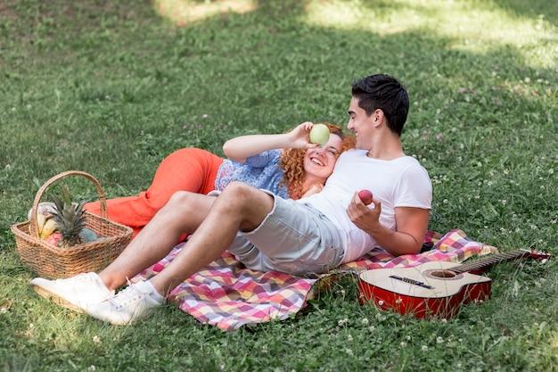 Leuk paar dat op een deken in het park rust Gratis Foto