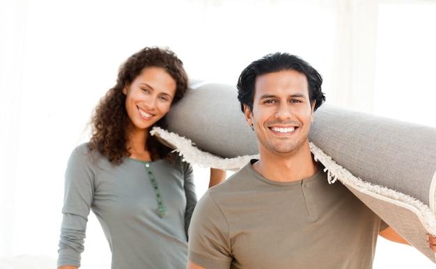 Leuk paar die een tapijt dragen die zich in de woonkamer bevinden Premium Foto