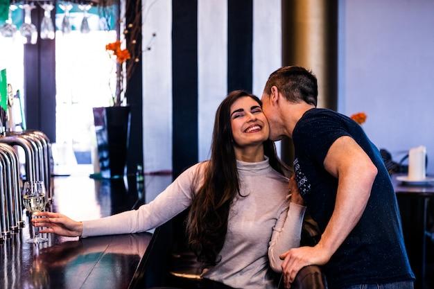 Leuk paar die en een drank in een bar kussen hebben Premium Foto