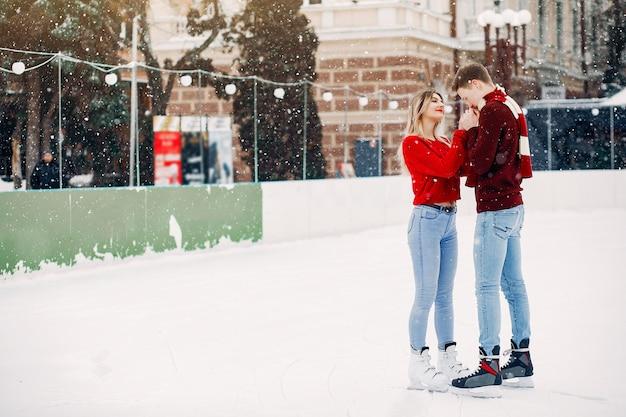 Leuk paar in rode sweaters die pret in een ijsarena hebben Gratis Foto