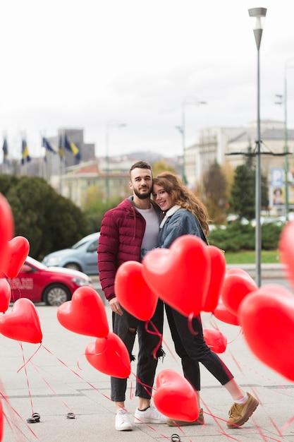 Leuk paar omringd door hart ballonnen Gratis Foto