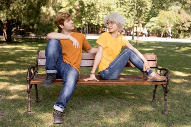Leuk paar ontspannen in het park op de bank Gratis Foto