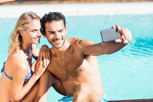 Leuk paar selfie nemen bij het zwembad Premium Foto