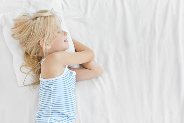 Leuk rustgevend kind dat op wit hoofdkussen in bed ligt, dat prettig slaapt, goede dromen en gelukkige uitdrukking heeft. mooie kleine jongen rustend op witte bed cover, goede nachtrust. jeugd concept Gratis Foto