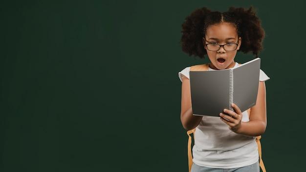 Leuk schoolmeisje dat haar aantekeningen leest Premium Foto