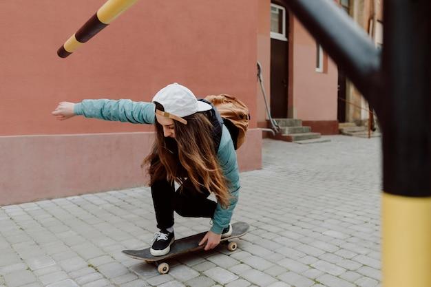 Leuk skatermeisje en haar skateboard Premium Foto