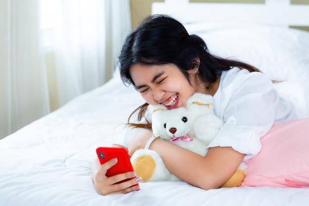 Leuk tienervrouw blij met smartphone op bed Gratis Foto