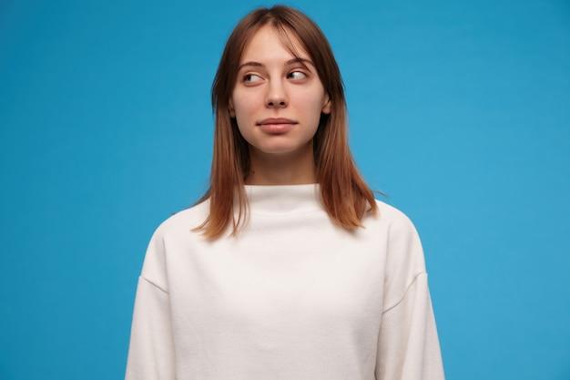 Leuk uitziende vrouw, mooi meisje met donkerbruin haar. witte trui dragen. mensen concept. casual ogend. verdacht naar links kijken naar kopie ruimte, geïsoleerd over blauwe muur Gratis Foto