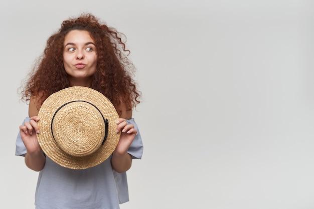 Leuk uitziende vrouw, mooi meisje met rood krullend haar. een gestreepte blouse met blote schouders dragen en een hoed vasthouden. een gezicht trekken. kijken naar rechts op kopie ruimte, geïsoleerd over witte muur Gratis Foto
