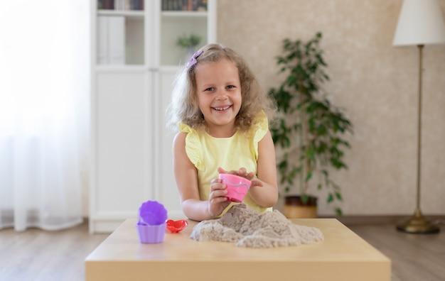 Leuk weinig glimlachend meisje die met kinetisch zand spelen Premium Foto