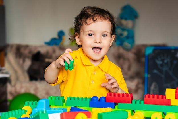 Leuk weinig jongenskind die thuis met kleurrijke kubussen spelen Premium Foto