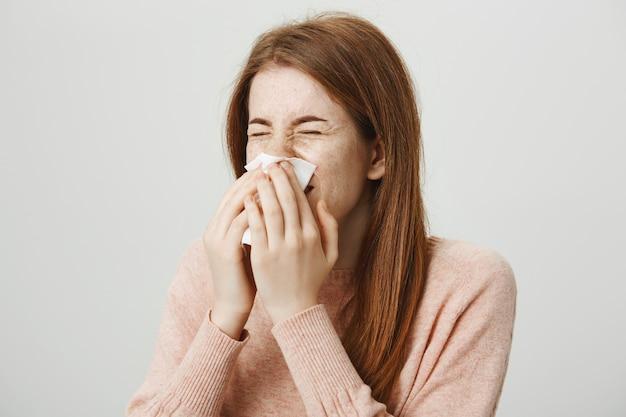 Leuk ziek roodharigemeisje met allergie die in servet niezen Gratis Foto