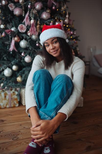 Leuke afro-amerikaanse vrouw zit in de buurt van een kerstboom, die zich voordeed op camera Gratis Foto