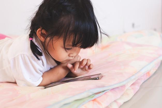 Leuke aziatische babymeisje het spelen smartphone liggend op haar bed in haar ruimte Premium Foto