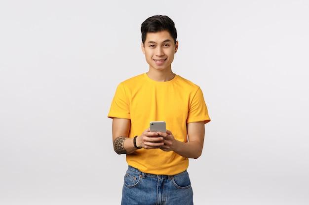 Leuke aziatische man in geel t-shirt met behulp van smartphone Premium Foto